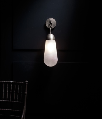 APPARATUS – LARIAT SCONCE ON BLACK PANEL WITH CHAIR